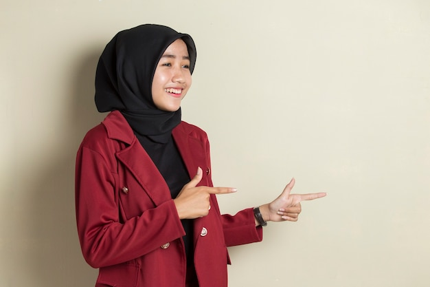 Young asian business woman wearing hijab smiling confident pointing with fingers to different directions.