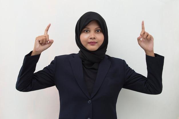 다른 방향으로 손가락으로 가리키는 자신감 미소 hijab를 착용하는 젊은 아시아 비즈니스 여자 광고 공간 복사