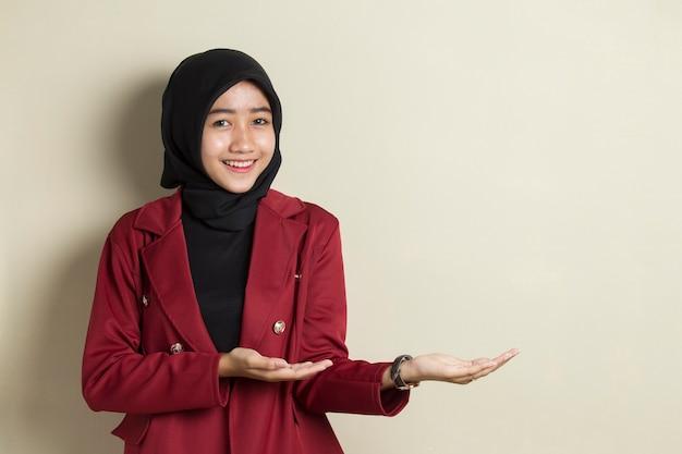 Молодая азиатская бизнес-леди носить хиджаб улыбается уверенно указывая пальцами в разные стороны.