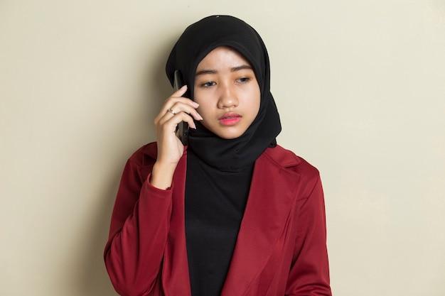 電話で話すヒジャーブを身に着けている若いアジアのビジネス女性