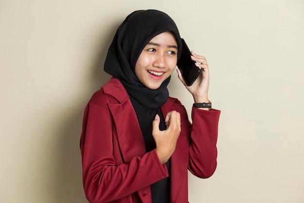 Молодая азиатская бизнес-леди в хиджабе разговаривает по телефону