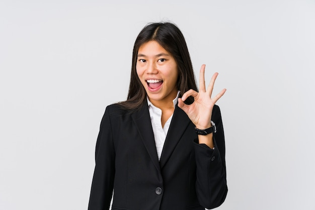 Молодая азиатская бизнес-леди подмигивает и держит ладный жест рукой.