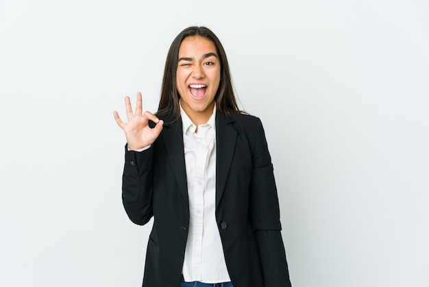 Young asian business woman winks an eye and holds an okay gesture with hand.
