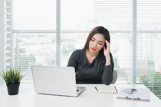 疲れた目と頭痛を持つ若いアジアのビジネス女性