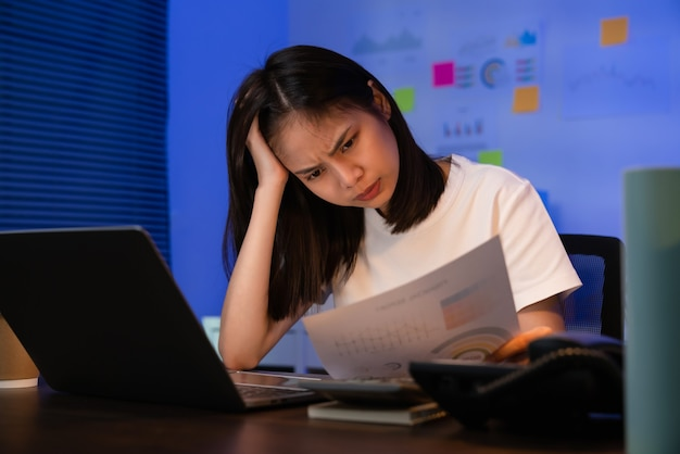 ラップトップで作業している若いアジアのビジネスウーマンは、夜のオフィスで片頭痛のために頭痛がします。
