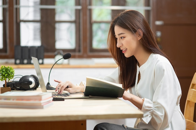 Young asian business woman working with internet using laptop computer sit at apartment
