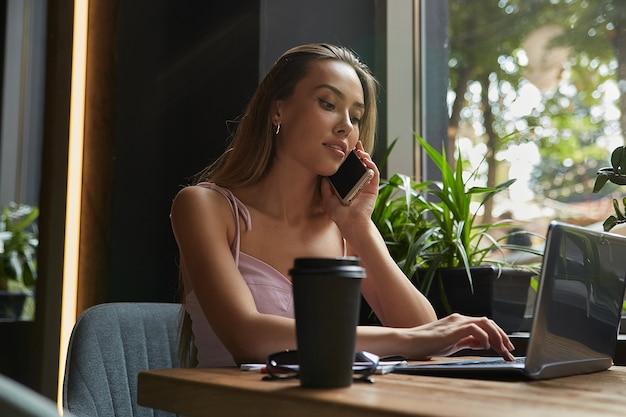 ノートパソコンに取り組んでいるカフェでノートにメモを書く若いアジアのビジネス女性