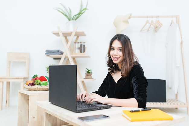 Young asian business women working with computer laptop at her shop