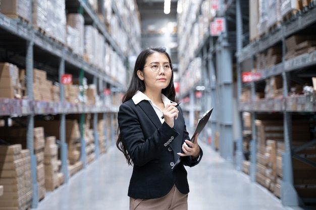 Young asian business worker, owner, entrepreneur woman holding file looking side up above shelf