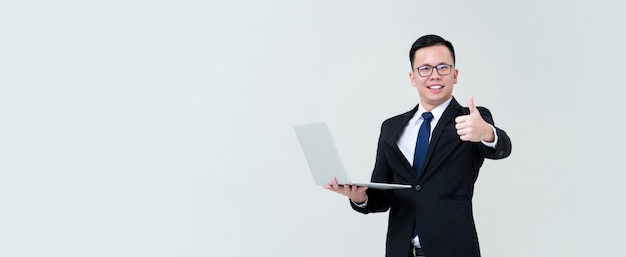 Young asian businessman being happy with his online business carrying laptop and giving thumbs up