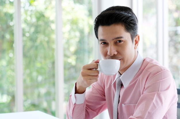 Young asian businessman drinking coffee at office