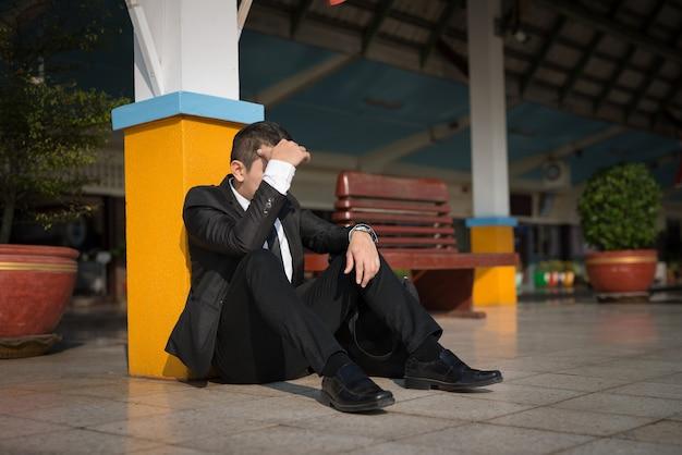 Молодой азиатский бизнесмен чувствует стресс, беспокоит головную боль, разочаровывает во время работы