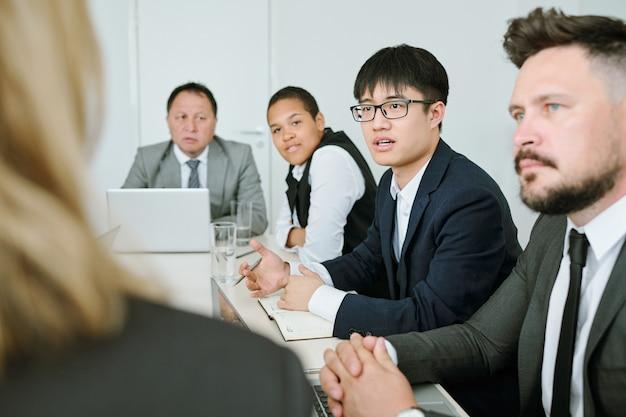 회의에서 이문화 동료들 사이에 앉아 비즈니스 코치에게 질문하는 정장 차림의 젊은 아시아 사업가