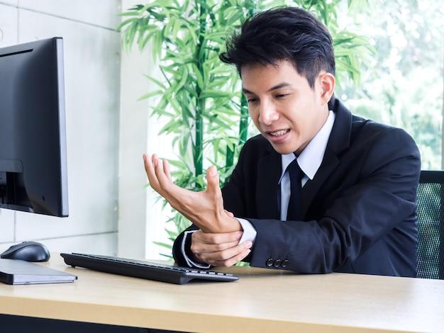 スーツを着た若いアジア人ビジネスマンがオフィスでノートパソコンを使用中に手の痛みを感じる