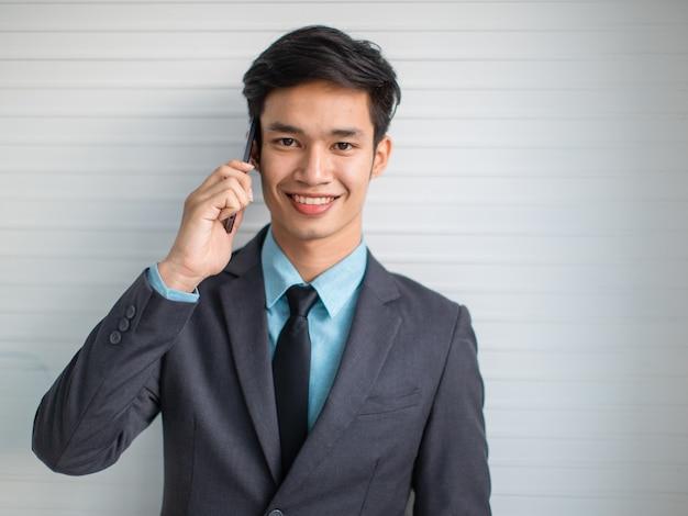 携帯電話で話し、笑顔の灰色の壁でカメラを見てスーツの若いアジアの実業家