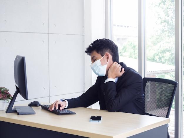 사무실에서 노트북 컴퓨터를 사용하는 동안 의료 얼굴 마스크 점점 손 통증을 입고 소송에서 젊은 아시아 사업가
