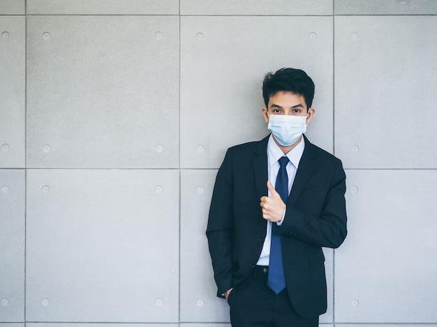 회색 벽에 엄지 손가락을 포기하는 의료 얼굴 마스크를 착용하는 소송에서 젊은 아시아 사업가