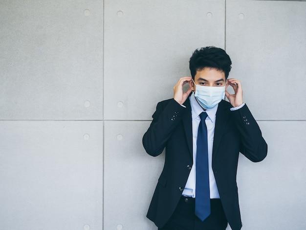 사무실에서 회색 벽 배경에 의료 얼굴 마스크를 쓰고 소송에서 젊은 아시아 사업가