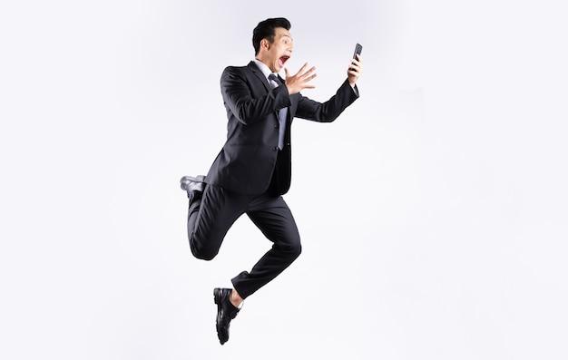 Молодой азиатский бизнесмен прыгает на белом