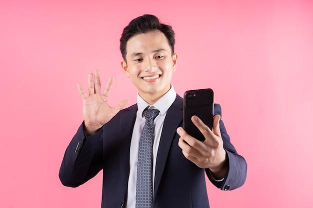 Молодой азиатский бизнесмен на розовом
