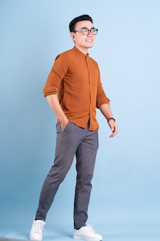 Young asian businessman posing on blue background