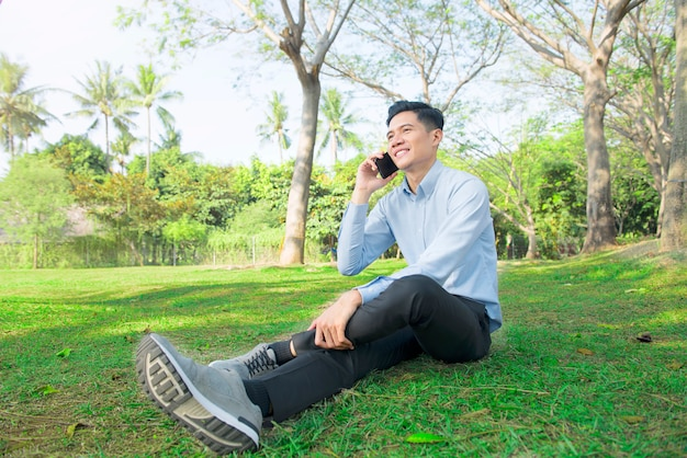 Young asian businessman relaxing while talking on mobile phone