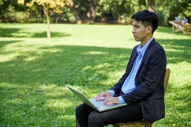 A young asian businessman sitting in the garden for work