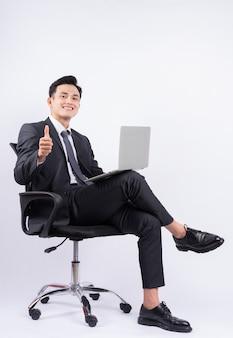 白の椅子に座っている若いアジア人実業家