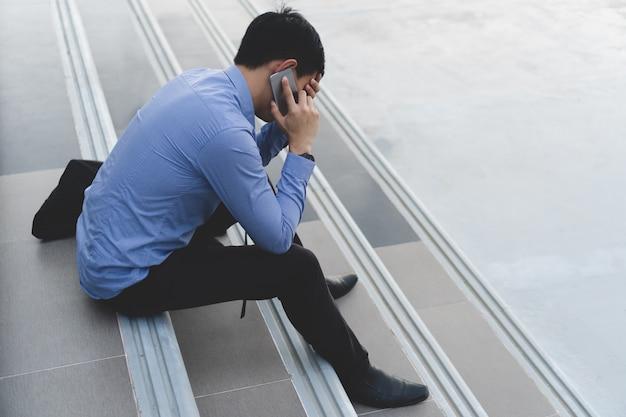전화 통화하는 계단에 앉아 젊은 아시아 사업가 강조하고있다.