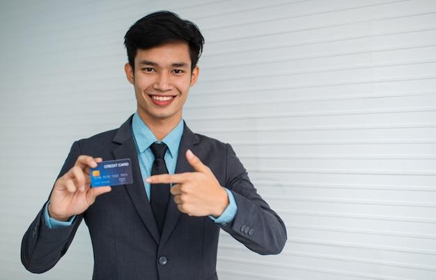 に対してクレジットカード広告銀行サービスを指しているカメラに微笑んでいる若いアジア人実業家