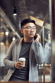 Молодой азиатский бизнесмен, выступая на смартфон в офисе
