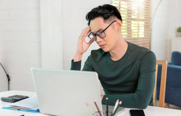 Время молодого азиатского бизнесмена напряженное работая на компьтер-книжке дома. работа из дома концепции.
