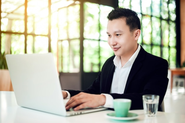 Young asian businessman in suit sitting at table in cafe using laptop computer with cup of coffee and looking to the laptop display.