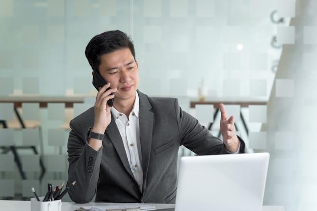 オフィスでラップトップを持っている顧客と電話で話している若いアジアのビジネスマン。
