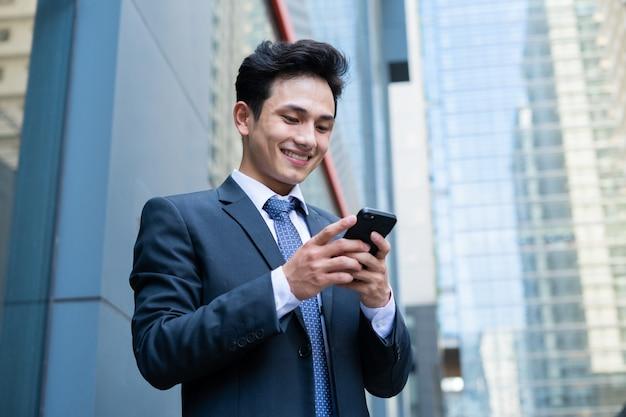 문자 메시지에 스마트 폰을 사용 하여 젊은 아시아 사업가