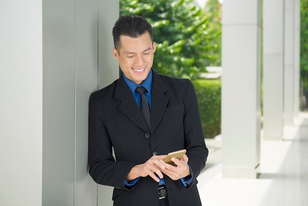 Young asian businessman using smartphone with relax