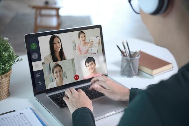 若いアジア人ビジネスマンは、自宅から離れた場所で作業するヘッドフォンと、同僚のビジネスマンとの仮想ビデオ会議を着用しています。ホームオフィスの概念での社会的距離。