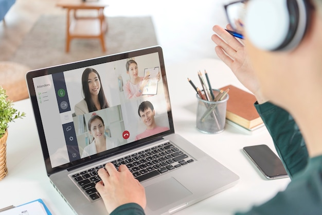 Young asian businessman wear headphones working remotely from home and virtual video conference meeting with colleagues business people. social distancing at home office concept.