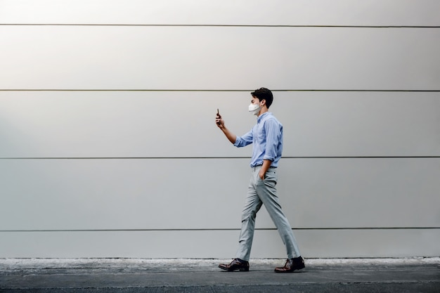 外科用マスクを着用し、都市の建物の壁を歩きながらスマートフォンを使用してアジア系の若いビジネスマン。