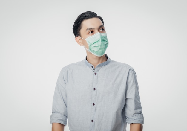 Young asian businessman wearing hygienic mask and looking up to prevent infection, 2019-ncov or coronavirus. airborne respiratory illness such as pm 2.5 fighting and flu isolated on white wall