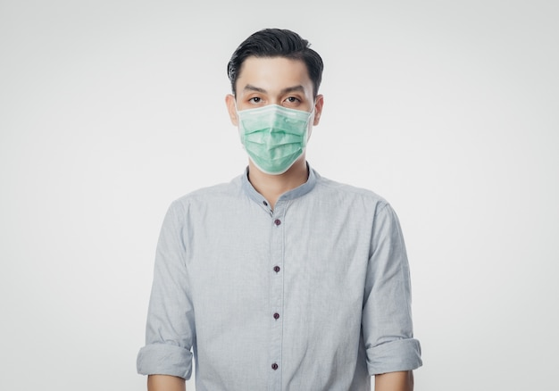 Young asian businessman wearing hygienic mask to prevent infection, 2019-ncov or coronavirus. airborne respiratory illness such as pm 2.5 fighting and flu isolated on white wall