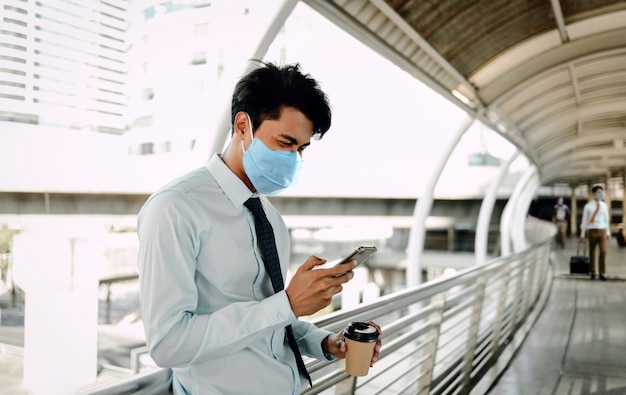 Young asian businessman wearing a surgical mask and using a smart phone in city.