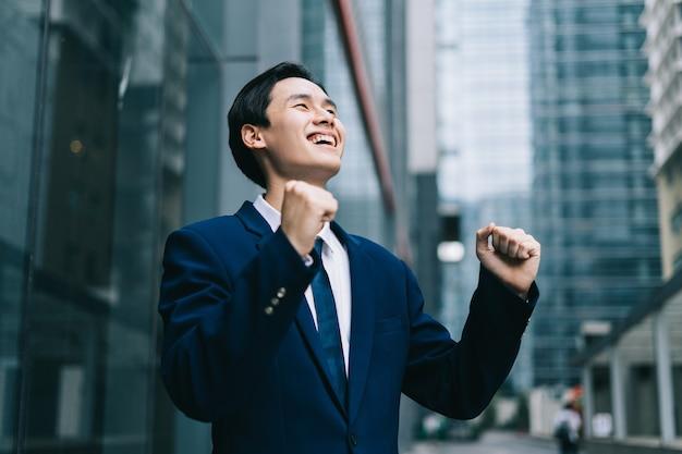 Молодой азиатский бизнесмен со стеклянным зданием