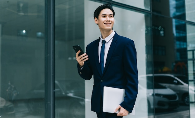 Young asian businessman with glass building