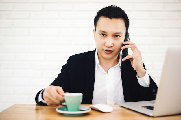 Young asian businessman working with laptop in the modern office, talking on the phone with his hand still holding a cup of coffee.