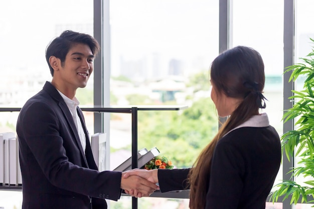 Young asian businessmen join hands with business women in the office.