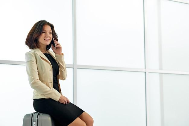 トロリーと空港で若いアジアの実業家