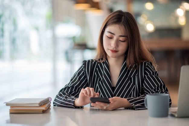 Молодая азиатская коммерсантка красивая очаровательная улыбается и использует на мобильном телефоне в офисе