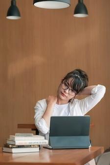 Молодая азиатская коммерсантка чувствует боль в шее после долгой работы на компьтер-книжке компьютера. концепция офисного синдрома.