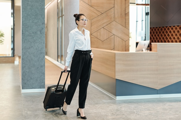 Young asian businesswoman in formalwear pulling suitcase while waiting for receptionist in hotel lounge